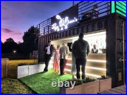 Shipping container cocktail bar elegant design fully lit up with roof garden